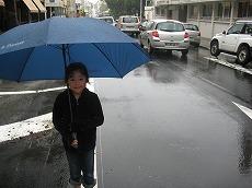 【写真左】ホテルで傘を借りてヌーメア市内へ。前日は温かく海で泳げたのに、フード付きパーカー着用です
